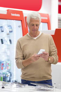Senior man looking at cell phone in electronics storeの写真素材 [FYI02121111]