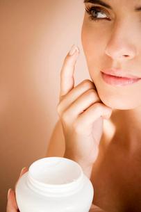 Woman applying moisturising cream to her faceの写真素材 [FYI02121113]