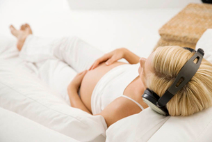 A pregnant woman relaxing listening to musicの写真素材 [FYI02121133]