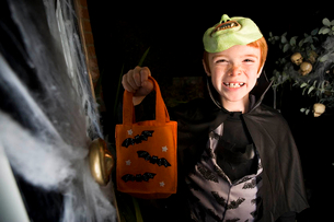 Boy in costume at a Hallowe'en party, holding an orange party bagの写真素材 [FYI02121149]