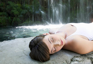 A woman relaxing by a waterfallの写真素材 [FYI02121163]