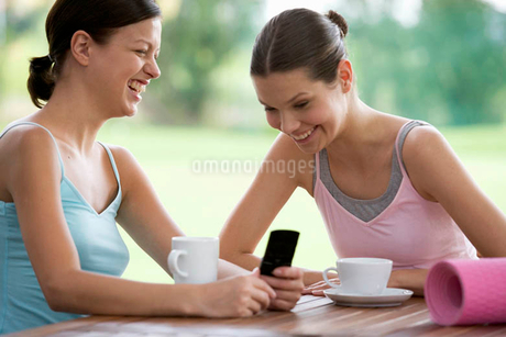 Two young women drinking coffee after a yoga classの写真素材 [FYI02121180]
