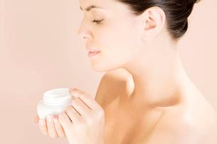 Woman holding a pot of moisturising creamの写真素材 [FYI02121182]