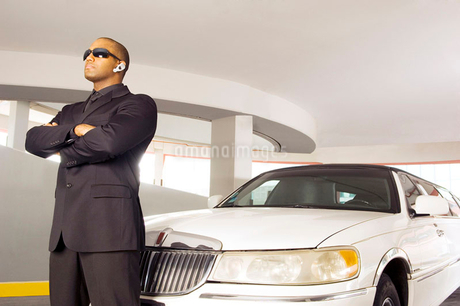 A chauffer standing by a stretch limousineの写真素材 [FYI02121199]