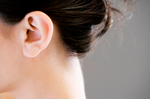 Ear and neck of a woman with dark hair up in a bunの写真素材 [FYI02121200]