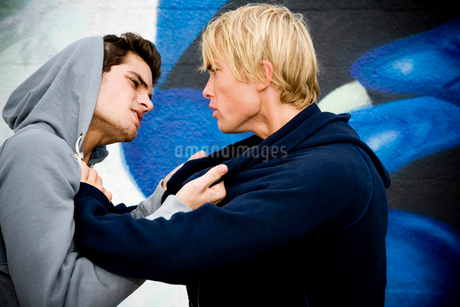Two men fighting in front of a graffiti covered wallの写真素材 [FYI02121201]