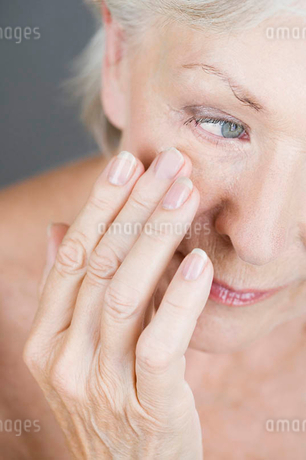 A senior woman touching the skin underneath her eyeの写真素材 [FYI02121209]