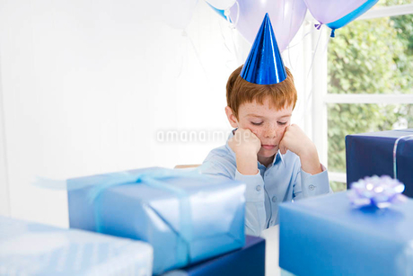 boy looking sad at birthday partyの写真素材 [FYI02121222]