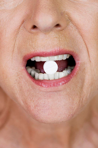 A senior woman with a pill between her teethの写真素材 [FYI02121234]