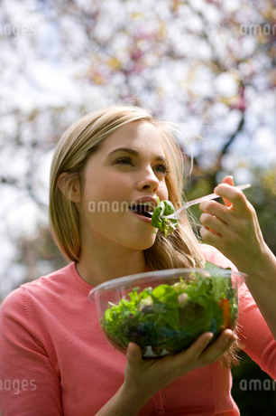 A young woman eating a bowl of salad in a parkの写真素材 [FYI02121238]