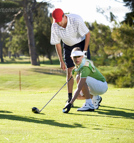 Man teaching a woman how to play golfの写真素材 [FYI02121247]