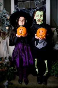 Children in Hallowe'en costumes, holding pumpkins with carved facesの写真素材 [FYI02121251]