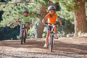 Boy and girl riding mountain bikes in woodsの写真素材 [FYI02121258]