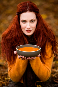 A young woman holding a bowl of soupの写真素材 [FYI02121288]