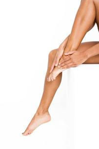 Woman rubbing her feet, applying moisturiserの写真素材 [FYI02121289]