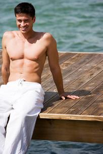 Topless man sunbathing on a jettyの写真素材 [FYI02121304]