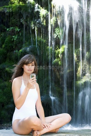 A woman drinking a glass of water by a waterfallの写真素材 [FYI02121335]
