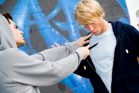 Confrontation between two young men and a group of friends in front of a graffiti covered wallの写真素材 [FYI02121366]