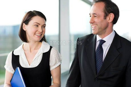 Male and female business colleagues chatting in office buildingの写真素材 [FYI02121371]