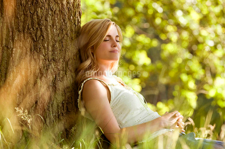 A young woman leaning against a tree, restingの写真素材 [FYI02121386]