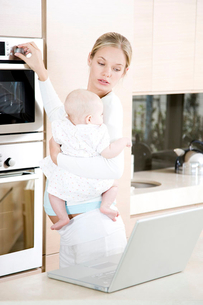 Young mother multi-tasking - holding baby, cooking dinner and looking at laptopの写真素材 [FYI02121389]