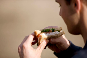 A young man eating a sandwich, close-upの写真素材 [FYI02121397]