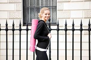 A mid adult woman carrying a yoga mat, walkingの写真素材 [FYI02121400]