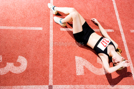 Portrait of a female athlete resting  and sitting on the running trackの写真素材 [FYI02121423]