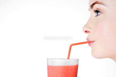A Young Woman Drinking A Fruit Drink Through A Strawの写真素材 [FYI02121456]