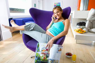 Young pregnant woman with magazine in armchair, using telephone, smiling, portraitの写真素材 [FYI02121479]