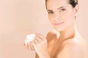 Woman holding a pot of moisturising creamの写真素材 [FYI02121481]