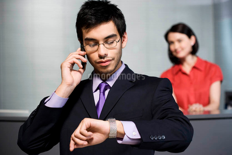Businessman making a call on his mobile phone at receptionの写真素材 [FYI02121492]