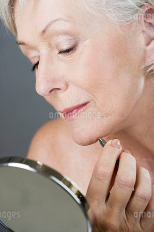 A senior woman plucking hairs from her chin with tweezersの写真素材 [FYI02121509]