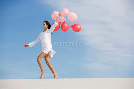 A woman walking in the desert holding a bunch of balloonsの写真素材 [FYI02121518]