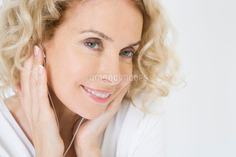 A middle-aged woman listening to mp3 music playerの写真素材 [FYI02121527]