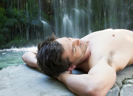 A man relaxing by a waterfallの写真素材 [FYI02121529]