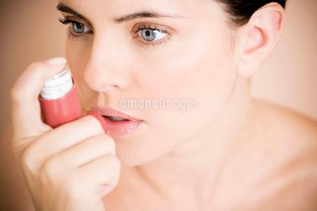 Female asthma sufferer using an inhalerの写真素材 [FYI02121549]