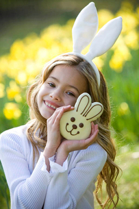 A young girl holding a chocolate bunny, wearing bunny earsの写真素材 [FYI02121616]