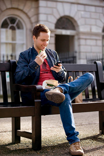A young man sitting on a bench, using his mobile phoneの写真素材 [FYI02121637]