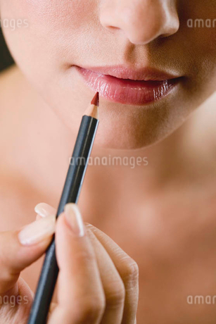 Woman using a lip pencilの写真素材 [FYI02121673]