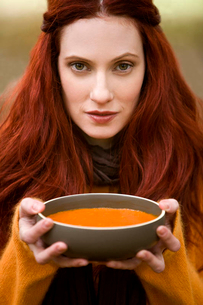 A young woman holding a bowl of soupの写真素材 [FYI02121693]