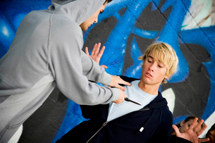 Confrontation between two young men in front of a graffiti covered wallの写真素材 [FYI02121722]