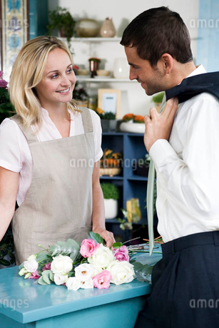 Man buying a bouquet of flowers in a florist's shop, flirting with the assistantの写真素材 [FYI02121725]
