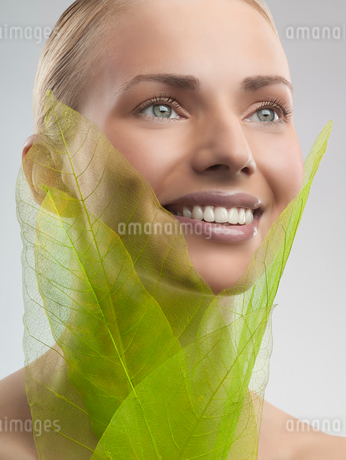 A woman holding green leaves made from netの写真素材 [FYI02121731]
