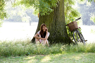 A young woman sitting under a tree talking on a mobile phoneの写真素材 [FYI02121745]
