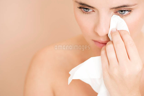 Woman crying, wiping tears away with a tissueの写真素材 [FYI02121746]