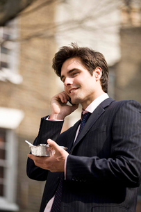 A businessman talking on his mobile phone, eating take-away foodの写真素材 [FYI02121754]