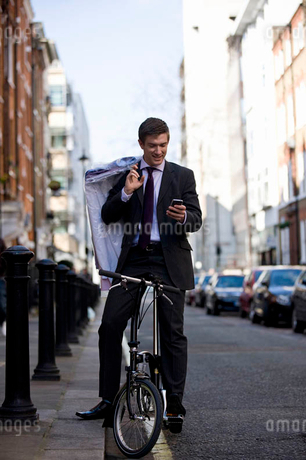 A businessman on his bicycle, looking at his phoneの写真素材 [FYI02121771]