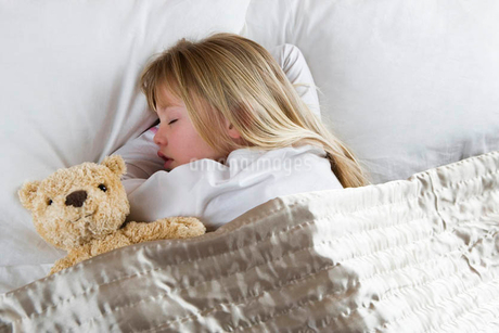 Young girl asleep in her bed with a teddy bearの写真素材 [FYI02121794]