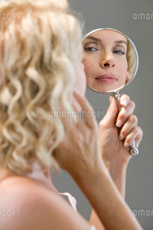 A middle-aged woman looking at her face in the mirrorの写真素材 [FYI02121816]